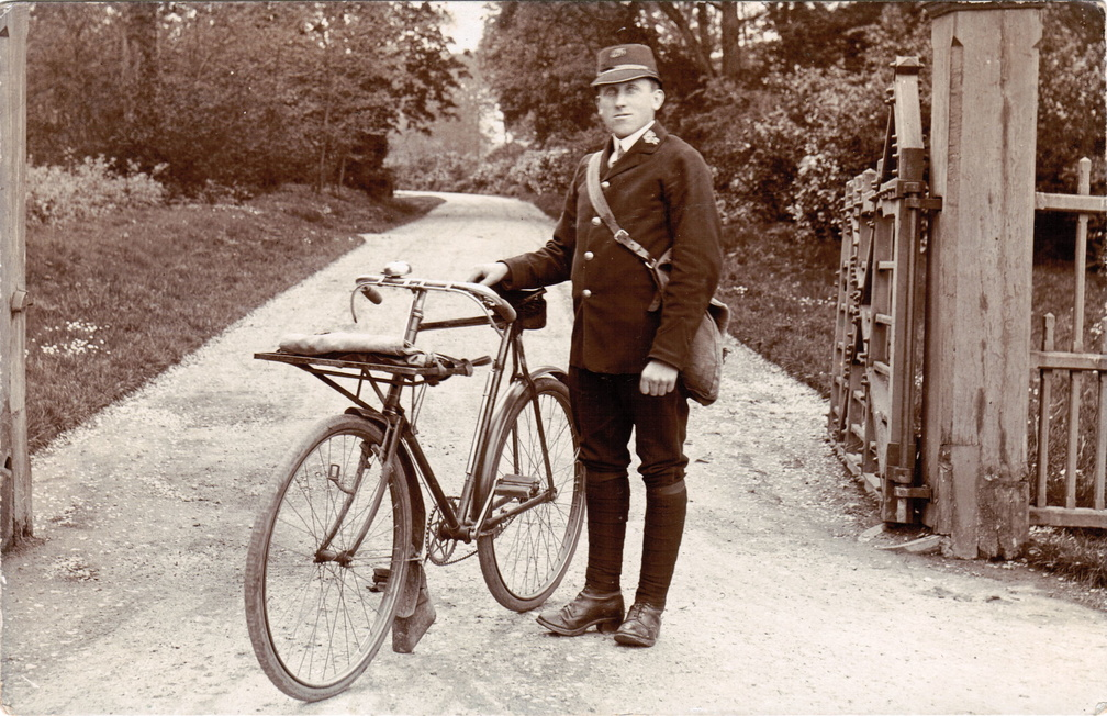 Charlie Curson, postman, with bicycle outside gateway and drive (? Barwick House), 1910s
