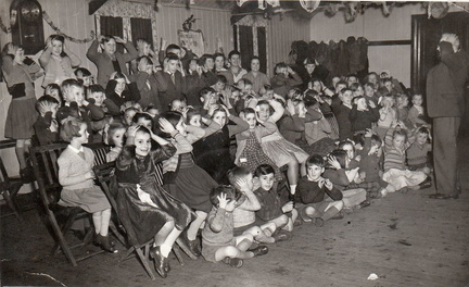 "Children's Christmas party put on by the WI in the WI Hut, around 1953.Rosemary Brown: ""We had a sit down tea, and games, and a present to take home with us. The party happened every year and was a highlight  for us all as times were hard then."""
