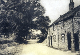 "Cross Lane looking north, Methodist Chapel in the distance.  Postcard, Raphael Tuck & Sons Ltd, captioned ""The Village, Stanhoe""."