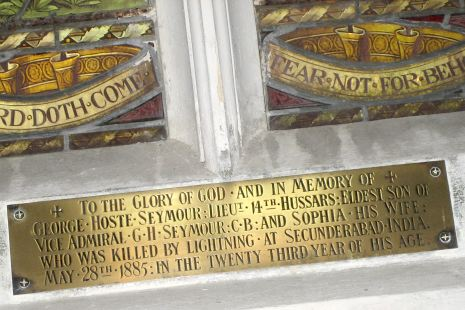 Brass plate beneath stained glass windows