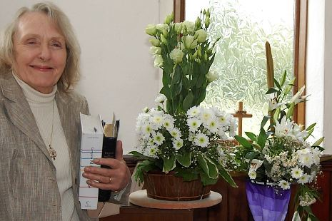 Organist Jill Johnson, with flowers, inside the church