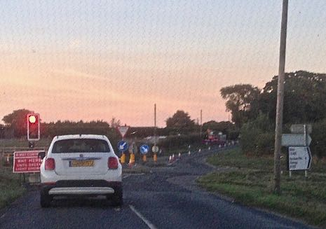 Stationary car, traffic lights and road signs on the approach to Stanhoe