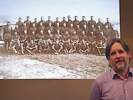Andrew Tatham in front of a projected image of the group of soldiers
