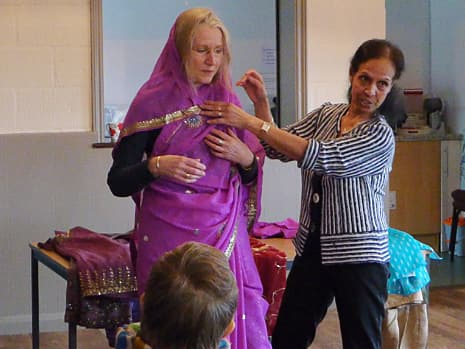 Junya Lewis and a friend demonstrate how to put on a sari